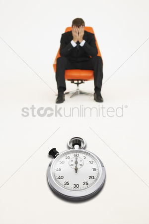 Loss : Worried businessman sitting on chair with stopwatch representing loss of time