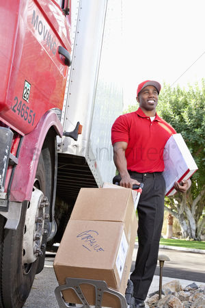 Pushing : Young african american male standing with packages near delivery truck
