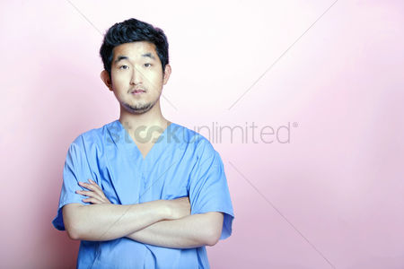 Proud : Young asian trainee doctor wearing scrubs