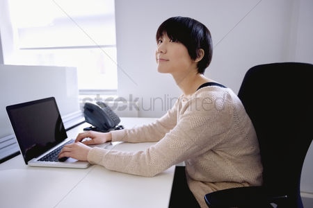 Portability : Young asian woman using laptop while looking away