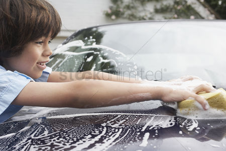 Transportation : Young boy  7-9  washing car with sponge side view