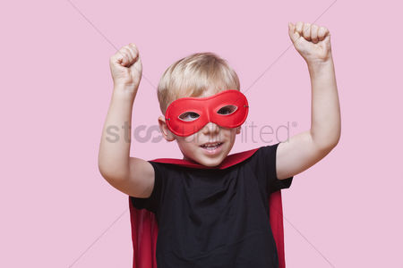 Pink : Young boy dressed in superhero costume with arms raised over pink background