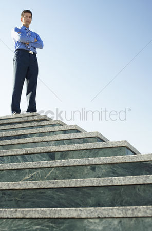 Steps : Young business man standing at top of steps low angle portrait
