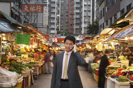 China : Young business man talking on mobile at street market