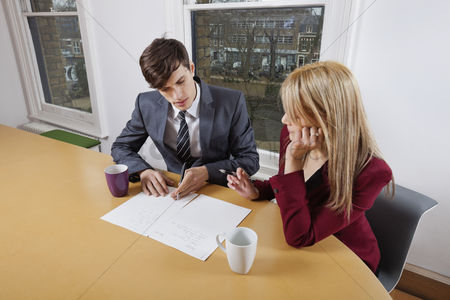 Window : Young businessman and female colleague with paperwork at conference table