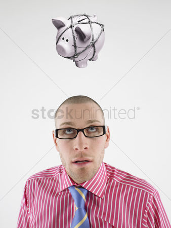 Rope : Young businessman looking up at piggy bank tied with rope representing trapped finances