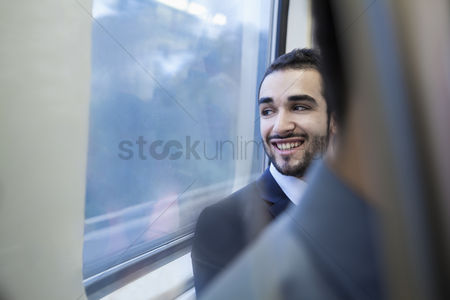 Interior : Young businessman smiling and looking out the window of the subway