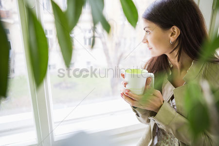 Women : Young businesswoman with coffee cup looking through window at office
