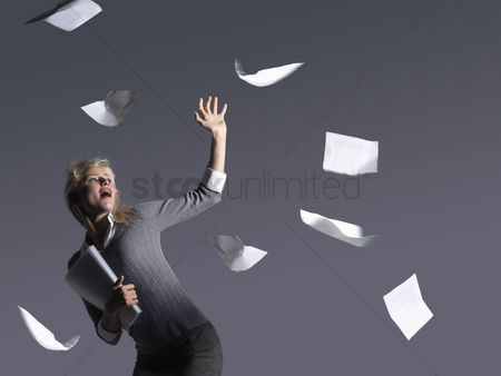 Loss : Young businesswoman with scattering papers side view