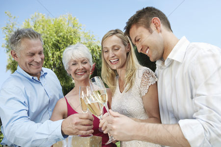 Toasting : Young couple and older couple toasting with champagne outside