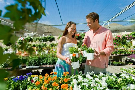 Husband : Young couple choosing potted flowers in garden centre