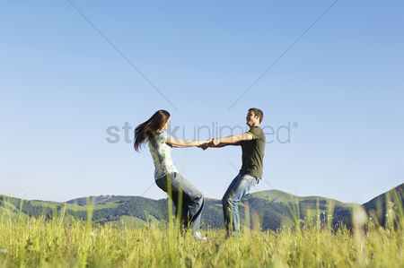 Denim : Young couple dancing in mountain field side view ground view