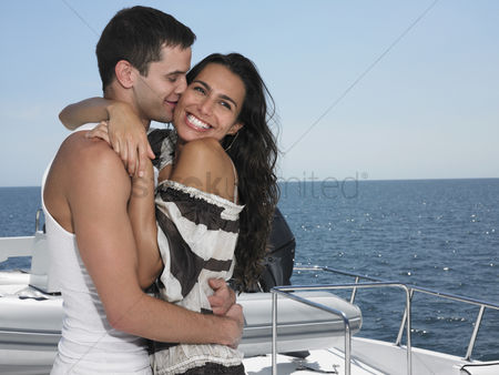 Kissing : Young couple embracing on yacht man kissing woman