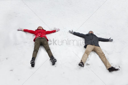Having fun : Young couple laying in snow making snow angels