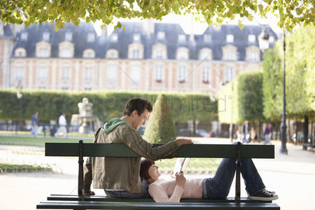 Sitting on lap : Young couple reading book sitting on bench in park