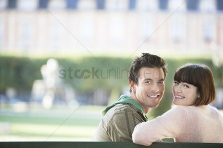 Mid adult man : Young couple sitting on bench head and shoulders in park