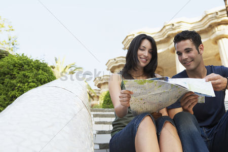 Staircase : Young couple sitting on stairs reading map portrait
