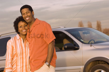 Moody : Young couple standing together in front of car half-length