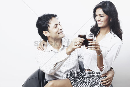 Sitting on lap : Young couple toasting with wine glasses