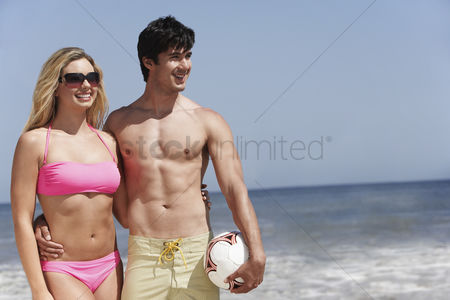 Girlfriend : Young couple with volleyball on beach