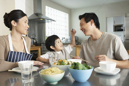 Young boy : Young family sitting at kitchen table interacting before meal