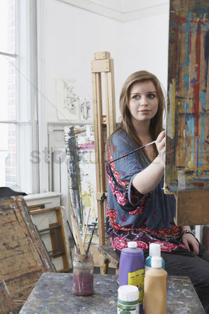 College : Young female art student painting at easel in art studio