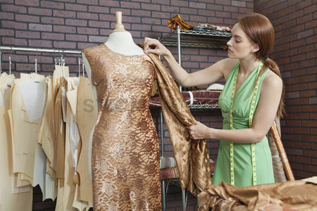 Match : Young female fashion designer matching cloth with fabric draped on tailor s dummy