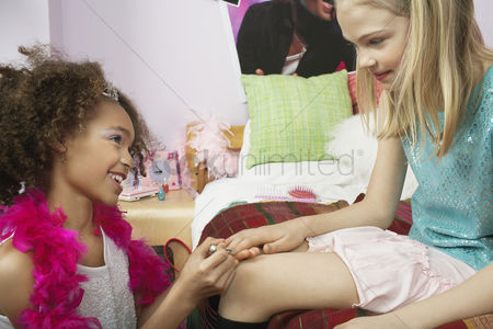 Maturity : Young girl applying nail polish to friends finger in bedroom