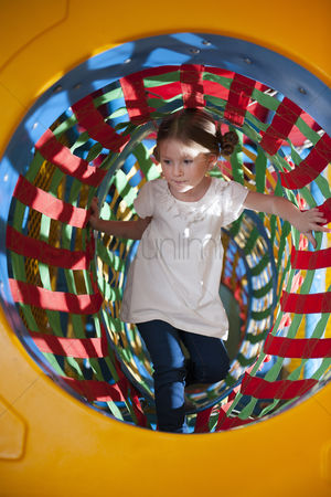 Excited : Young girl climbs through netted tunnel in soft play centre