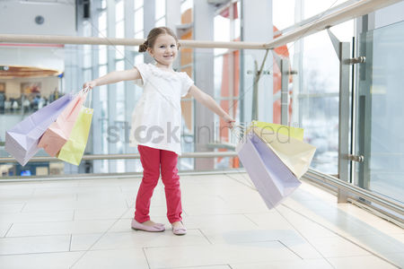 Offspring : Young girl laden with paper shopping bags