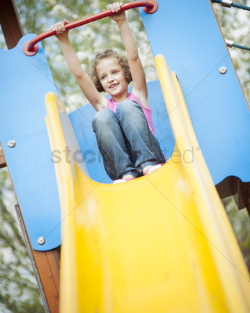 Excited : Young girl on slide in playground