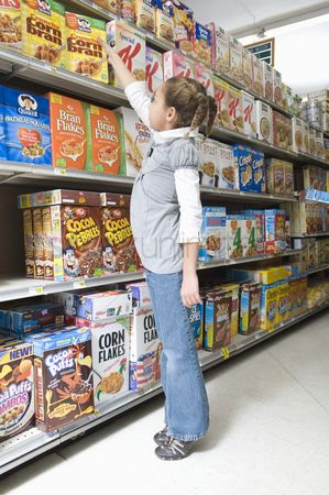 Supermarket : Young girl reaching for ceral product in supermarket aisle