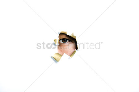 England : Young korean man looking through ripped paper hole