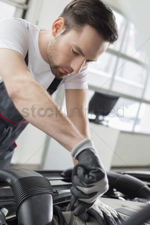 Car : Young maintenance engineer repairing car in automobile store