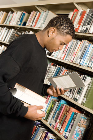 Choosing : Young man choosing books in library