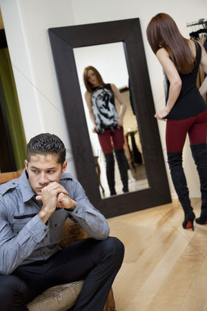 Spending money : Young man looking away while thinking with girlfriend in background looking at herself in mirror