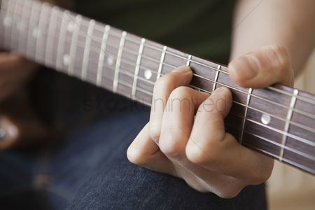 Hobby : Young man playes chord on guitar