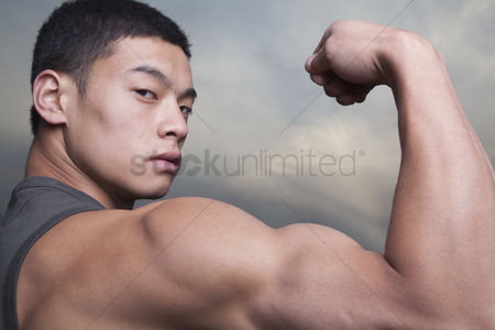 Arm raised : Young man showing off his bicep muscles