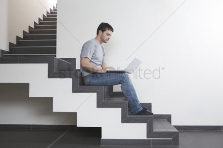 Staircase : Young man sits on staircase with laptop
