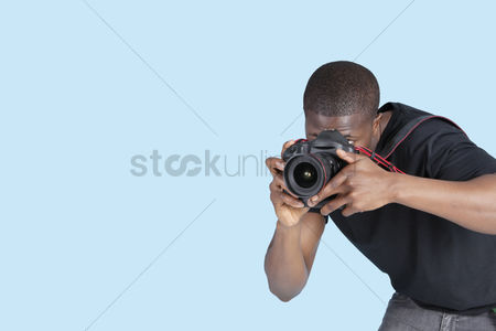 Camera : Young man taking photo through digital camera over blue background