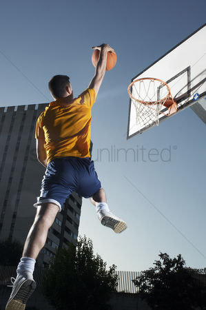 Arm raised : Young man with basketball jumping towards hoop mid-air