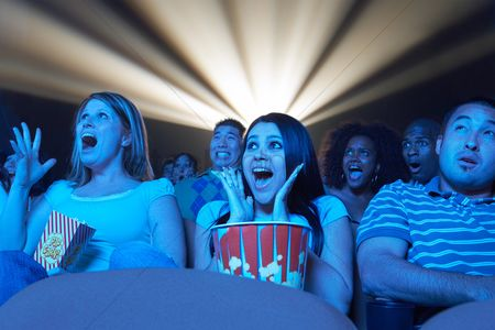 Friends : Young people screaming watching horror movie in theatre