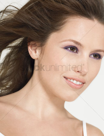 Head shot : Young smiling woman with wind-swept hair close up