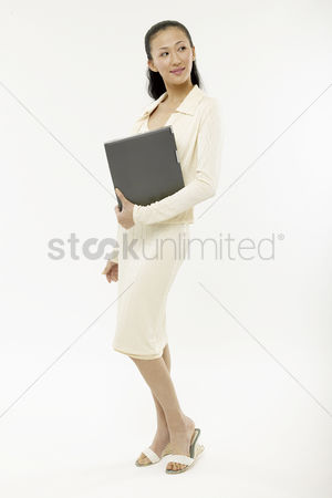 Interior : Young woman carring a notebook computer