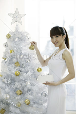 Ponytail : Young woman decorating christmas tree