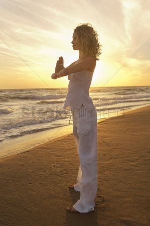 Curly hair : Young woman doing tai chi on beach side view