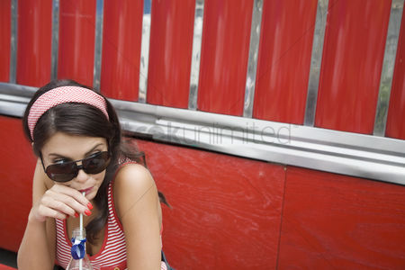 Posed : Young woman drinking a soda
