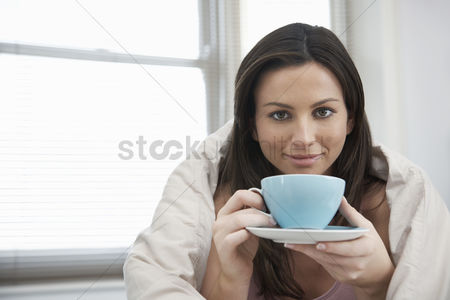 Comfort : Young woman drinking tea in bed portrait