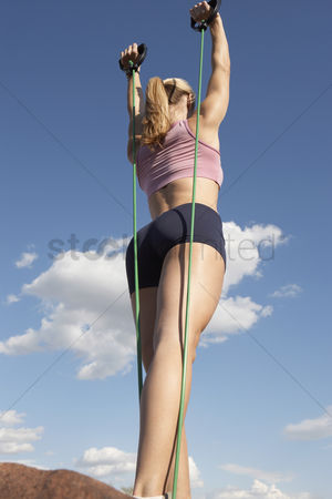 Arm raised : Young woman exercising outdoors low angle view