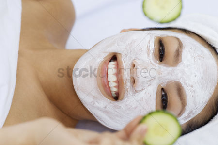 Club : Young woman having facial treatment holding cucumbers portrait
